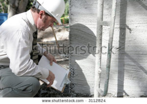 stock-photo-a-building-inspector-checking-out-the-foundation-of-a-new-building-3112824